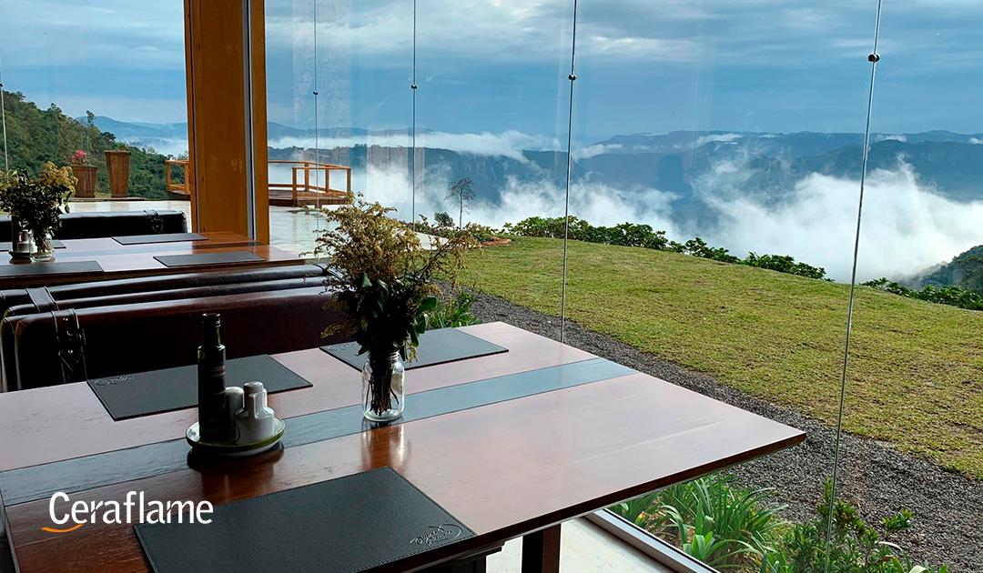 comer com os olhos 5 restaurantes com vistas incríveis: imagem de uma mesa em um restaurante no alto de uma montanha.